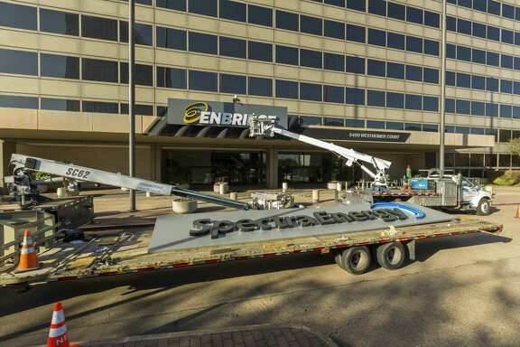 Workers install an Enbridge sign on the gas pipelines business unit center in Houston over the weekend.