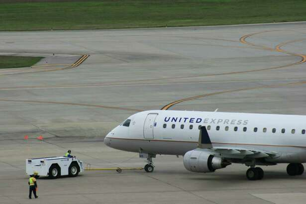 Workers prepare a United Express flight for departure at Bush Intercontinental Airport in February 2017. Mesa Airlines operates the Embraer E175.