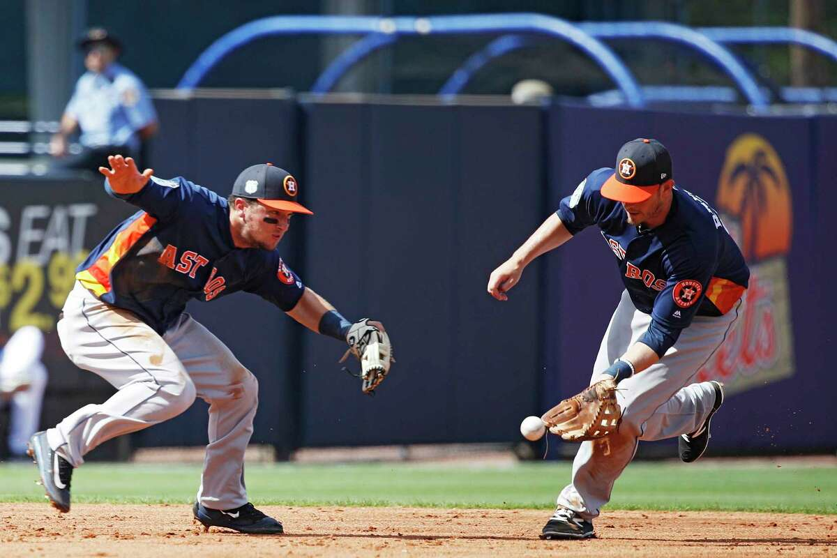 Astros third baseman Alex Bregman, left, pulls up to avoid distracting Reid Brignac as the shortstop fields a grounder against the Mets on Monday at Port St. Lucie, Fla. The Astros won 5-2, improving to 2-1 this spring.