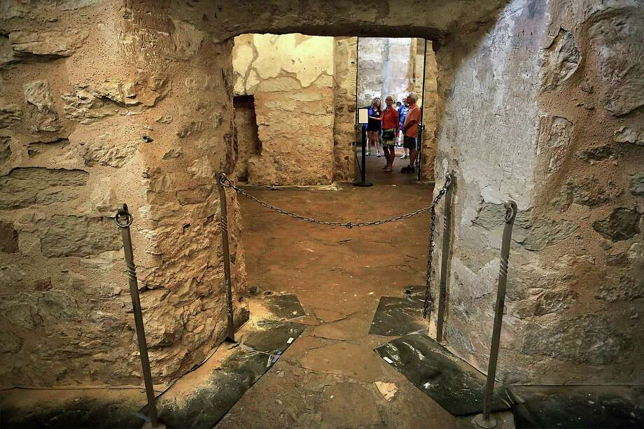 Visitors to the Alamo look into a chained-off room where strips of black paper have been put on the floor to collect parts of the wall that fall. Photo: Bob Owen /Staff Photographer / ©2017 San Antonio Express-News