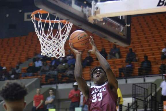 Silsbee Tigers Kalon Barnes (33) catches a pass and shoots during a game between North Forest and Silsbee Monday at the Johnson Coliseum in Huntsville, Feb. 27, 2017.