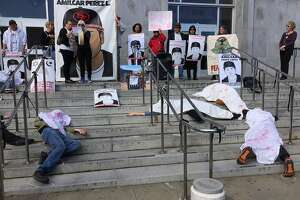 Activists stage a die-in at San Francisco's Hall of Justice on Monday, Feb. 27, 2017, in honor of the two-year anniversary of Amilcar Perez-Lopez's death. Perez-Lopez, 21, was fatally shot by two San Francisco police officers in the Mission District on Feb. 26, 2015.