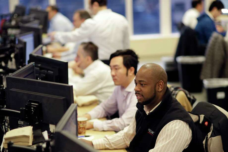 In this Jan. 12, 2017, photo, traders work on the Mizuho Americas trading floor in New York. Stocks are opening slightly lower on Wall Street, Monday, Feb. 27, 2017, following 11 straight gains for the Dow Jones industrial average. (AP Photo/Mark Lennihan) Photo: Mark Lennihan, STF / Copyright 2017 The Associated Press. All rights reserved.
