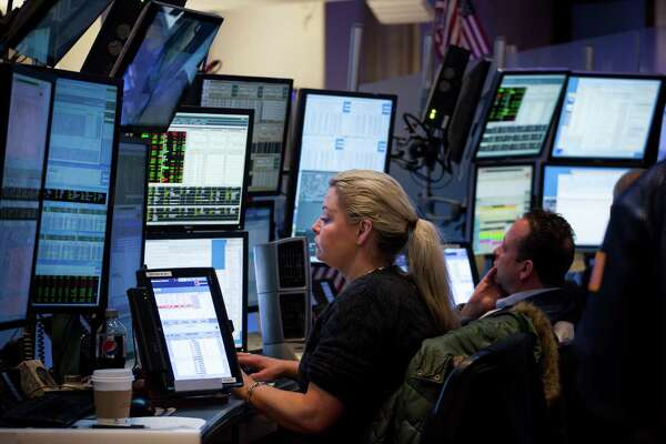 Traders work Monday on the floor of the New York Stock Exchange. The Dow Jones industrial average closed at a record high for the 12th consecutive time.
