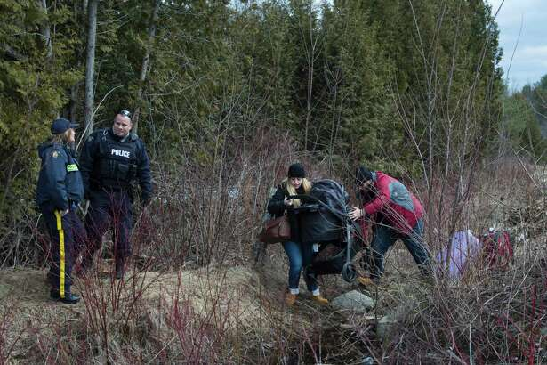 TOPSHOT - A couple who claimed to be from Turkey struggles to get their baby and baby carriage across the US/Canada border February 27, 2017, in Champlain, New York.  There continues to be an increasing number of people crossing the US border into Canada illegally. / AFP PHOTO / Don EMMERTDON EMMERT/AFP/Getty Images