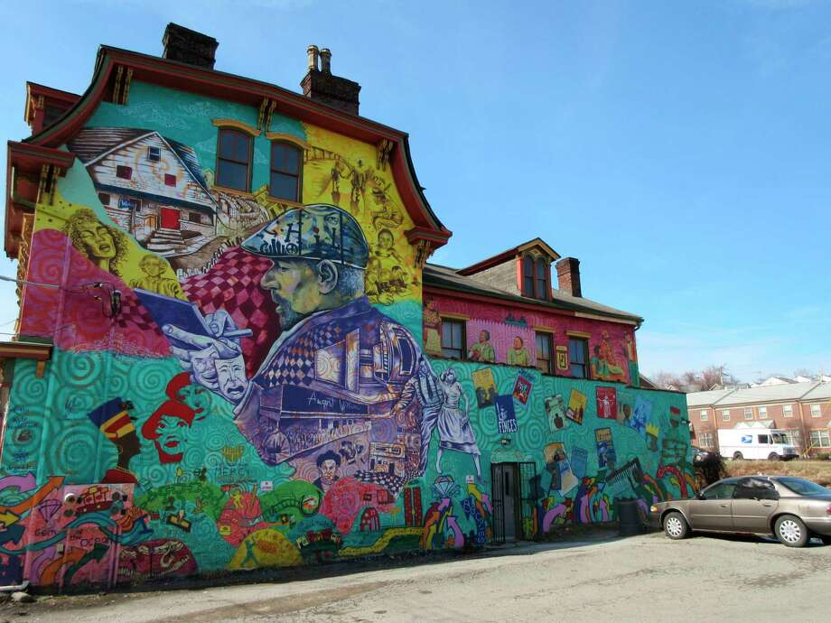 This Feb. 17, 2017 photo shows a colorful mural in the Hill District of Pittsburgh honoring playwright August Wilson and his work. The Hill District offers a rich map of places and stories connected to Wilson's plays, nine of which are set in Pittsburgh. Artist Kyle Holbrook created the mural with children from a local arts program. (AP Photo/Beth J. Harpaz) ORG XMIT: NYLS206 Photo: Beth J. Harpaz / Copyright 2017 The Associated Press. All rights reserved.