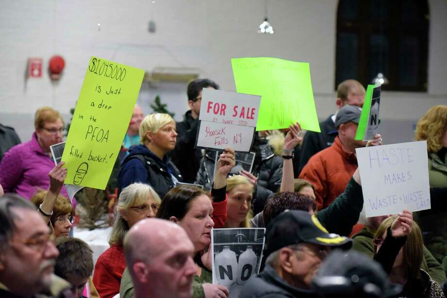 Residents opposed to a revised proposed PFOA settlement hold signs as they try to urge board members to vote no on the proposal during a Village of Hoosick Falls board meeting on Monday, Feb. 27, 2017, in Hoosick Falls, N.Y.  (Paul Buckowski / Times Union) Photo: PAUL BUCKOWSKI / 20039797A