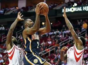 Indiana Pacers guard Rodney Stuckey, center, drives to the basket as Houston Rockets guard Patrick Beverley, left, and guard Louis Williams defend in the first half of an NBA basketball game, Monday, Feb. 27, 2017, in Houston. (AP Photo/Eric Christian Smith)