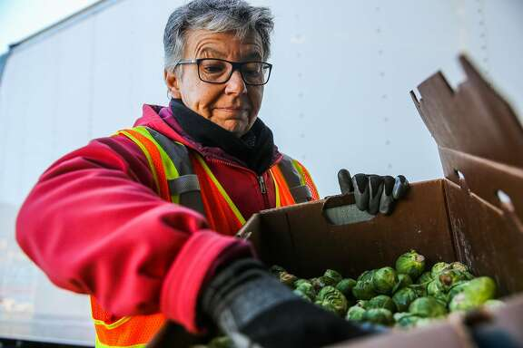 Carolyn Lasar checks the quality of brussel sprouts that are being donated at San Francisco's wholesale produce market in San Francisco, California, on Monday, Feb. 27, 2017.