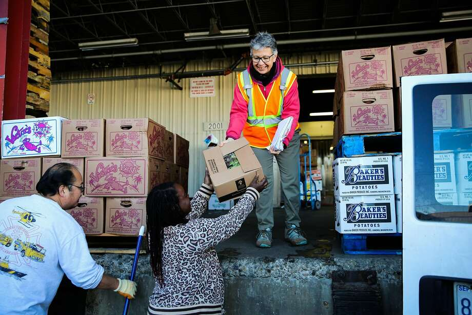 Carolyn Lasar (top) hands off a donated box of mesclun to Ebony Wilkerson of Catholic Charities at San Francisco's Wholesale Produce Market. Photo: Gabrielle Lurie, The Chronicle