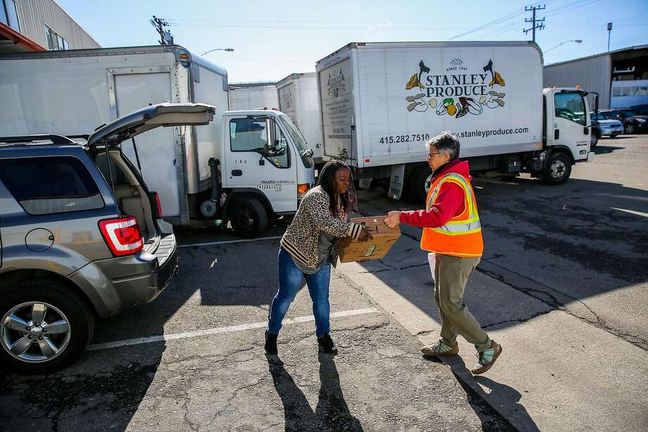 At S.F.'s Wholesale Produce Market, Carolyn Lasar (right) gives a box of donated greens to Ebony Wilkerson of Catholic Charities. Photo: Gabrielle Lurie, The Chronicle