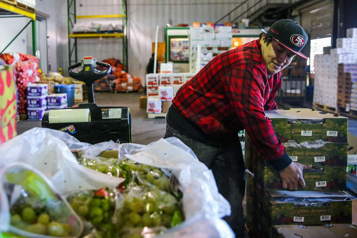 A porter who goes by Junior organizes grapes at the San Francisco's wholesale produce market in San Francisco, California, on Monday, Feb. 27, 2017.