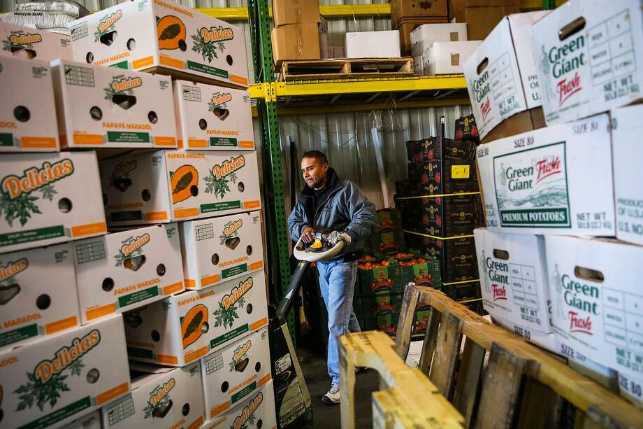 Noe Olivares moves boxes of papaya at S&L produce at the San Francisco Wholesale Produce Market. Photo: Gabrielle Lurie, The Chronicle
