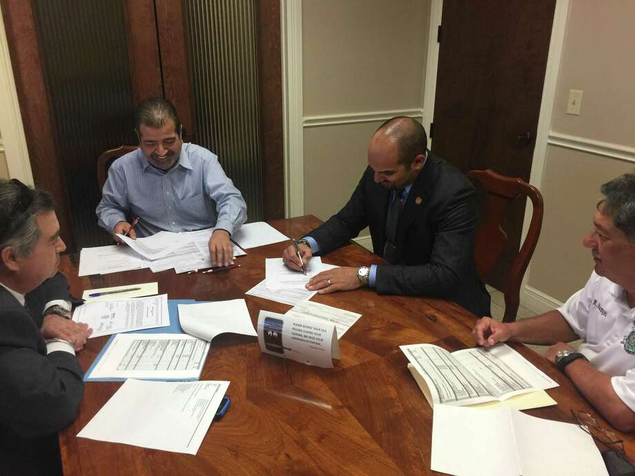 Webb County Judge Tano Tijerina signs the closing documents for a property where a Fire Department sub-station and emergency medical services will be built. Photo: Courtesy /Webb County