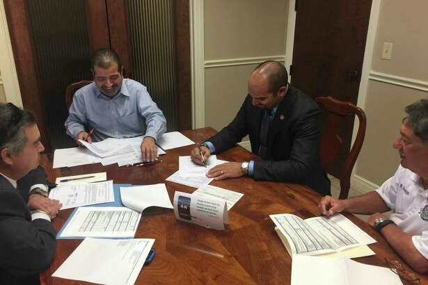 Webb County Judge Tano Tijerina signs the closing documents for a property where a Fire Department sub-station and emergency medical services will be built.