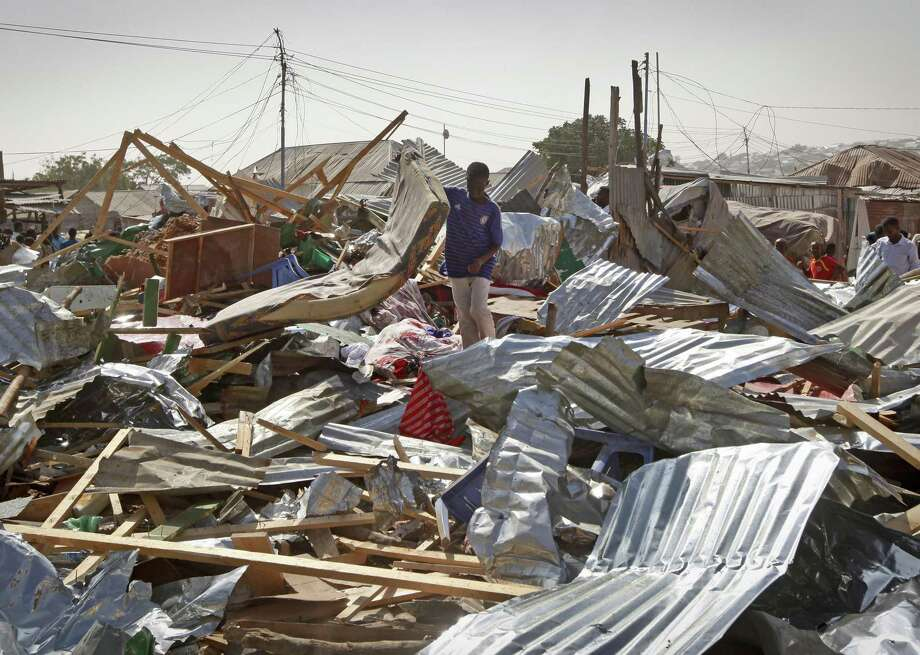 A shopkeeper surveys the wreckage of shops destroyed by a blast in a market in the capital Mogadishu, Somalia Sunday, Feb. 19, 2017. A Somali police officer says a blast at a busy market in the western part of Somalia's capital tore through shops and food stands and killed more than a dozen people and wounded many others. (AP Photo/Farah Abdi Warsameh) Photo: Farah Abdi Warsameh, STR / Associated Press / Copyright 2017 The Associated Press. All rights reserved.