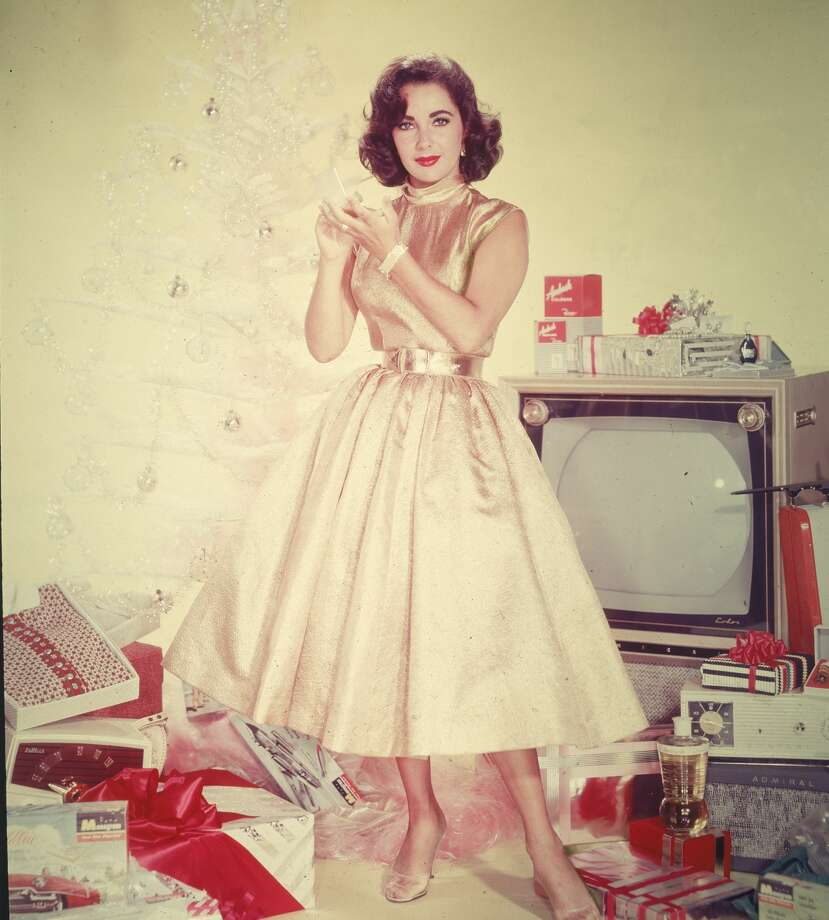 Publicity portrait of British-born actor Elizabeth Taylor in a yellow dress as she stands in front of an artificial Christmas tree amidst a pile of opened presents, including a television set, clothing, and a radio, circa 1950s. Photo: Hulton Archive/Getty Images