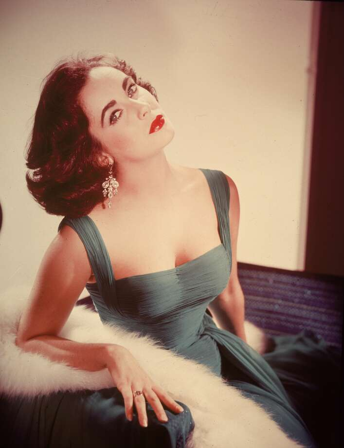 Elizabeth Taylor through the yearsPortrait of British-born actor Elizabeth Taylor in a form-fitting green dress as she sits with her head tilted back exposing her neck, circa 1950s. Photo: Hulton Archive/Getty Images
