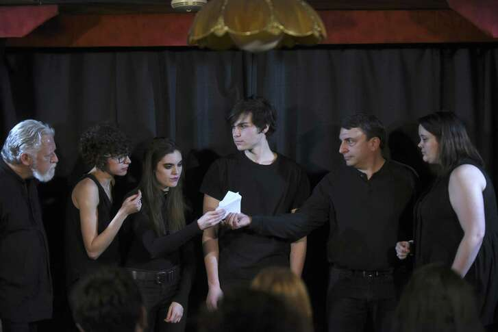 """LC Wilks, left, Casey Lynn, Gina Hughes, George Velez Cue, Scott Leibowitz and Tina Jackson read a list of audience suggestions onstage prior to their performance of """"After Life,"""" an improvised drama being produced by Alamo City Improv at the Magic Time Machine."""