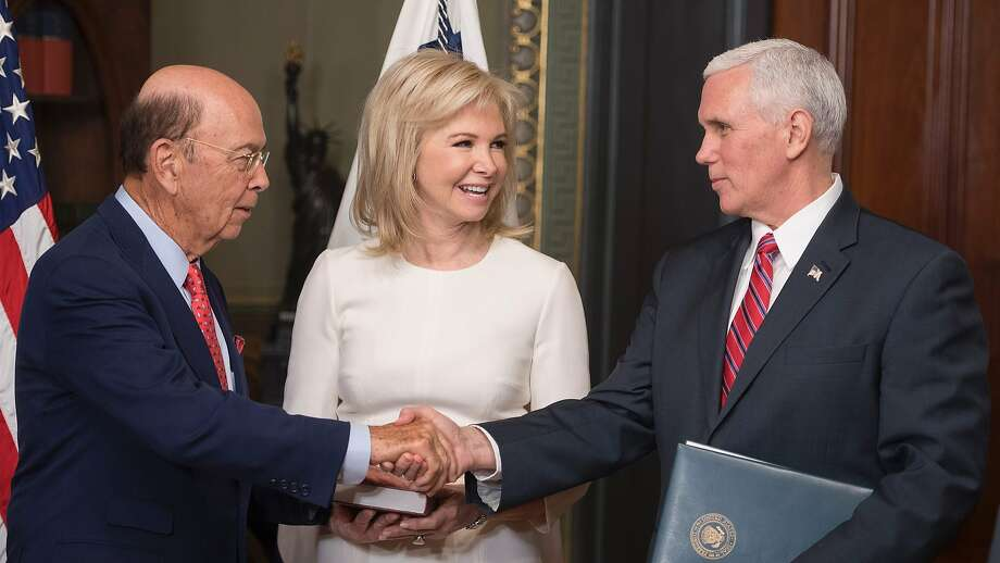 Commerce Secretary Wilbur Ross (left) shakes hands with Vice President Mike Pence after being sworn in with his wife, Hilary, by his side in Washington. Photo: JIM WATSON, AFP/Getty Images