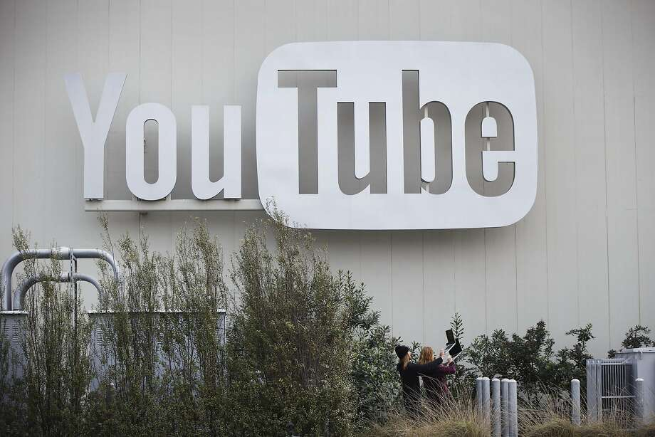 People hold up laptops while filming a video underneath signage outside a YouTube Inc. office in the Playa Vista neighborhood of Los Angeles. YouTube on Tuesday announced a new online television service for $35 a month that will compete against smaller subscription packages offered by cable companies. Photo: Patrick T. Fallon, Bloomberg
