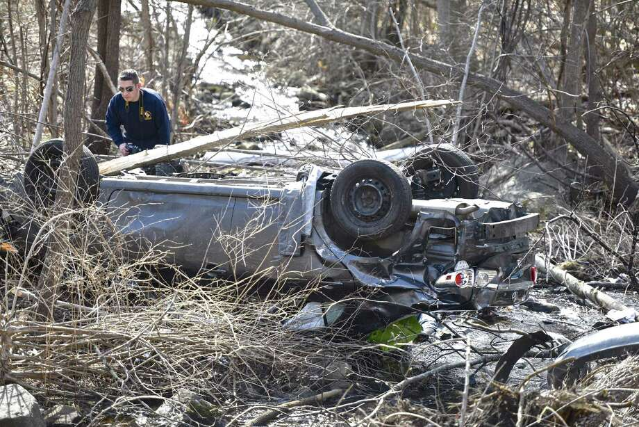 Albert Gorski, of the Connecticut State Police CARS Unit, photographs a car, which rolled over and slid down an embankment near the intersection of Route 202 and Baldwin Hill Road around 12:30 p.m. Tuesday killing one occupant. Four people were in the car and needed to be removed by first responders, said Sgt. Eric Haglund. Three were taken by ambulance to Danbury Hospital, said Washington Ambulance Association Chief Adam Woodruff. February 28, 2017, in Washington, Conn. Photo: H John Voorhees III / Hearst Connecticut Media / The News-Times