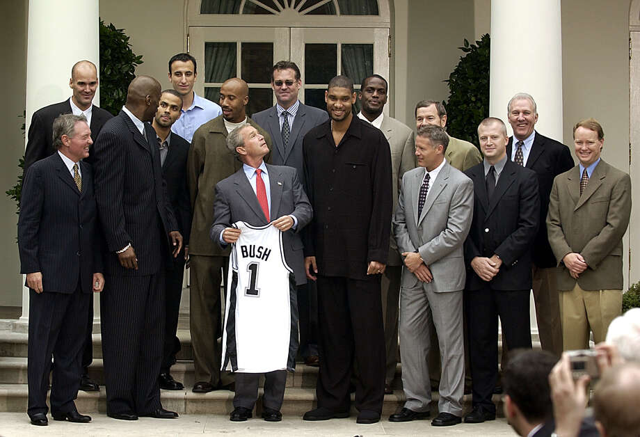 President Bush poses for a group photo with the NBA Champion San Antonio Spurs during a ceremony in the Rose Garden of the White House Tuesday, Oct. 14, 2003. Left to right are team owner Peter Holt, Danny Ferry, Kevin Willis, Tony Parker, Emanuel Ginobili, Bruce Bowen, Bush, general manager R. C. Buford, Tim Duncan, Malik Rose, assistant coaches Brett Brown, foreground, and P.J Carlesimo, trainer Will Sevening, head coach Gregg Popovich and assistant coach Mike Budenholzer. (AP Photo/Gerald Herbert)