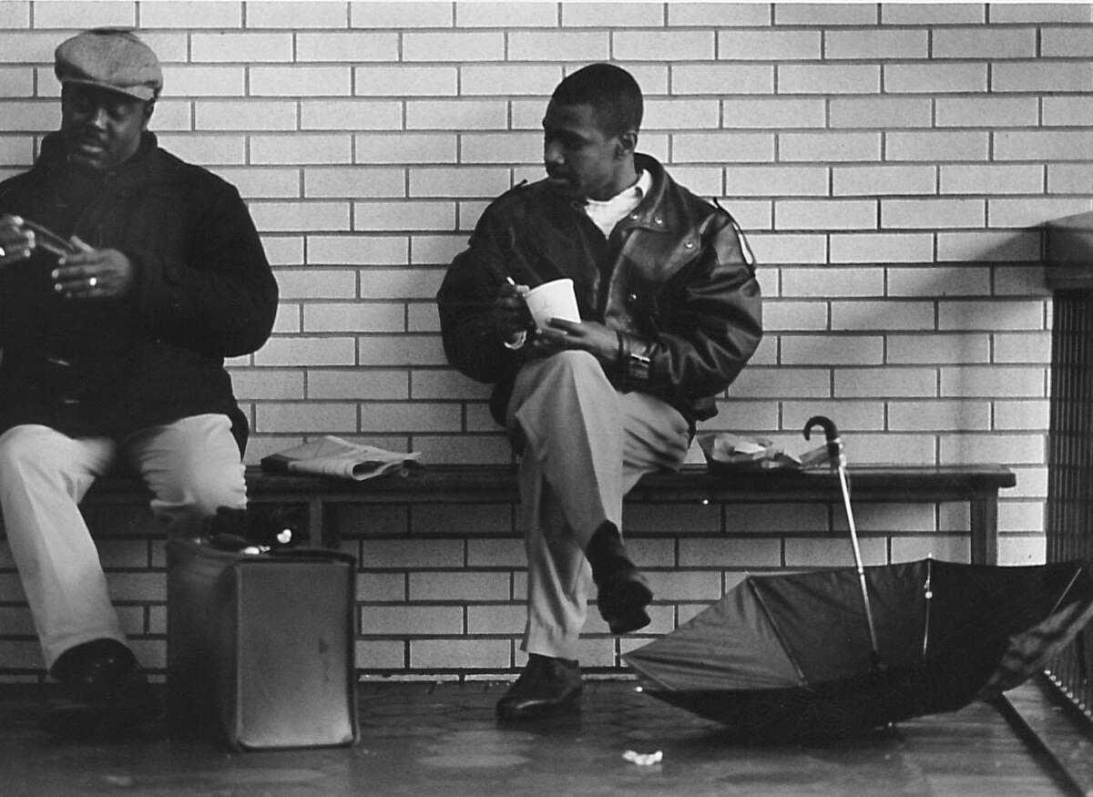 Wilber Senoble, left, and Etzer Bertand, right, enjoy lunch on the second level of the Greenwich train station on a rainy March 17, 1993.