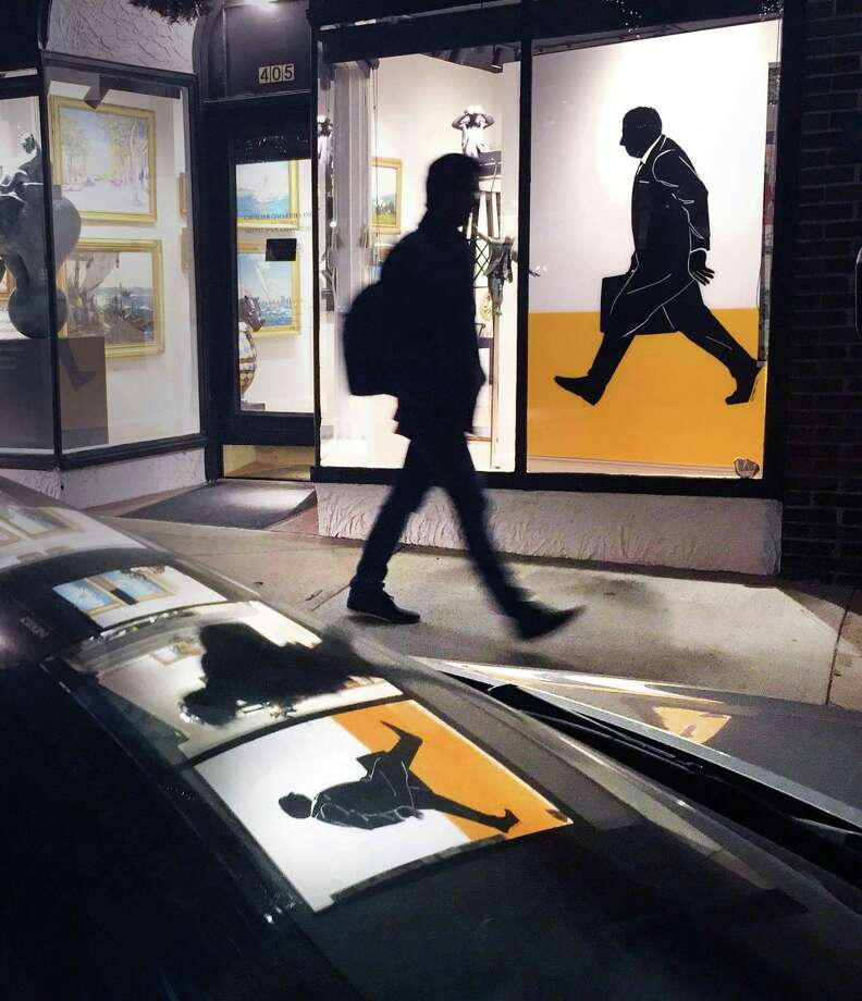 "The silhouette of a pedestrian walking past a downtown Greenwich art gallery brings to mind the old saying ""art imitating life,""  or is it ""life imitating art,"" as a silhouetted figure in an artwork is in a similar pose, on Greenwich Avenue, Friday night Dec. 23, 2016. Photo: Bob Luckey Jr. / Hearst Connecticut Media / Greenwich Time"