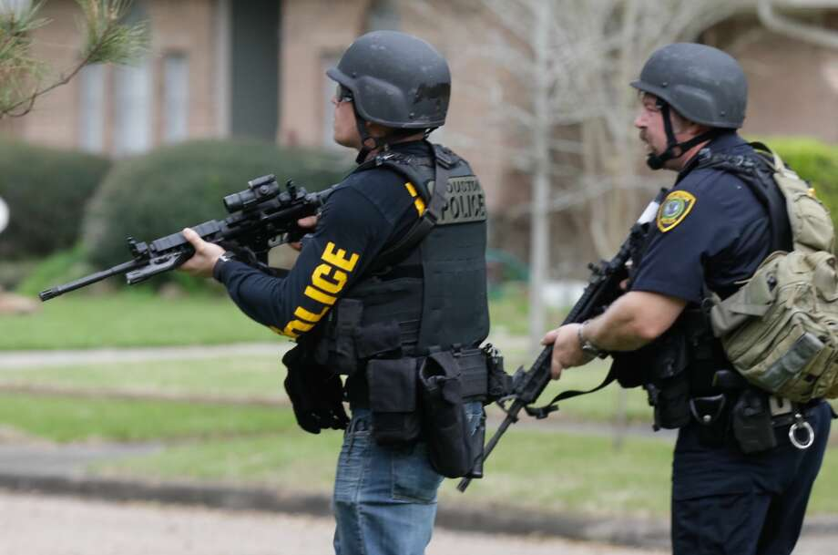 Police officers are shown searching in a neighborhood along Chadwell at Haverstock near the scene where two officers were shot Tuesday, Feb. 28, 2017.