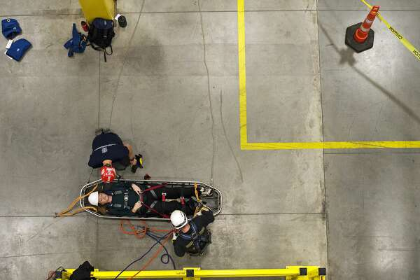 """ERIN KIRKLAND   ekirkland@mdn.net Xalt Energy human relations administrative assistant Sarah Howard waits for ropes to be removed after being lowered to the ground during a stokes basket operations rescue at a Rope Rescue Operations Level class on Thursday at Xalt Energy. This was the first time that the Midland County Fire Department and Michigan Urban Search and Rescue (MUSAR) have hosted this class. Eighteen local students from Saginaw, Bay and Midland Counties Technical Rescue Teams participated in the weeklong class which practiced various rescue situations and rappelling. """"I felt confident in their abilities,"""" Howard said."""