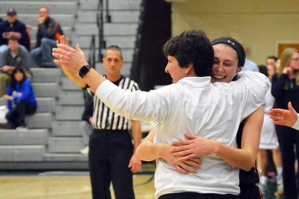 Edwardsville senior guard Makenzie Silvey hugs coach Lori Blade after coming off the court in the fourth quarter of Monday's super-sectional game against Lisle Benet Academy.