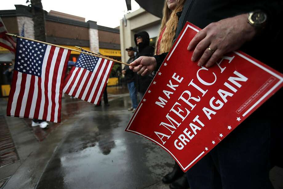 "Supporters of President Trump hold signs and American flags during a rally in favor of the ""America First"" agenda on Feb. 27 in Brea (Orange County). Photo: Justin Sullivan, Getty Images"