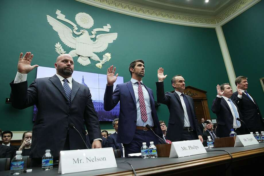 Shot-putter Adam Nelson (left to right), swimmer Michael Phelps, CEO of the U.S. Anti-Doping Agency Travis Tygart, World Anti-Doping Agency executive Rob Koehler, IOC executive Richard Budgett are sworn in during a Capitol Hill hearing. Photo: Alex Wong