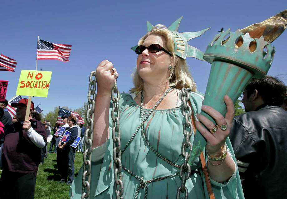 Tamara Schirr-macher displays chains representing the national debt at a 2009 tea party event in Pleasanton, Calif. Photo: Paul Sakuma, STF / AP
