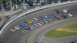 Ryan Blaney (21), front left, and Kyle Busch (18) lead a pack of drivers through Turn 4 during the NASCAR Daytona 500 auto race at Daytona International Speedway, Sunday, Feb. 26, 2017, in Daytona Beach, Fla. (AP Photo/Phelan M. Ebenhack)