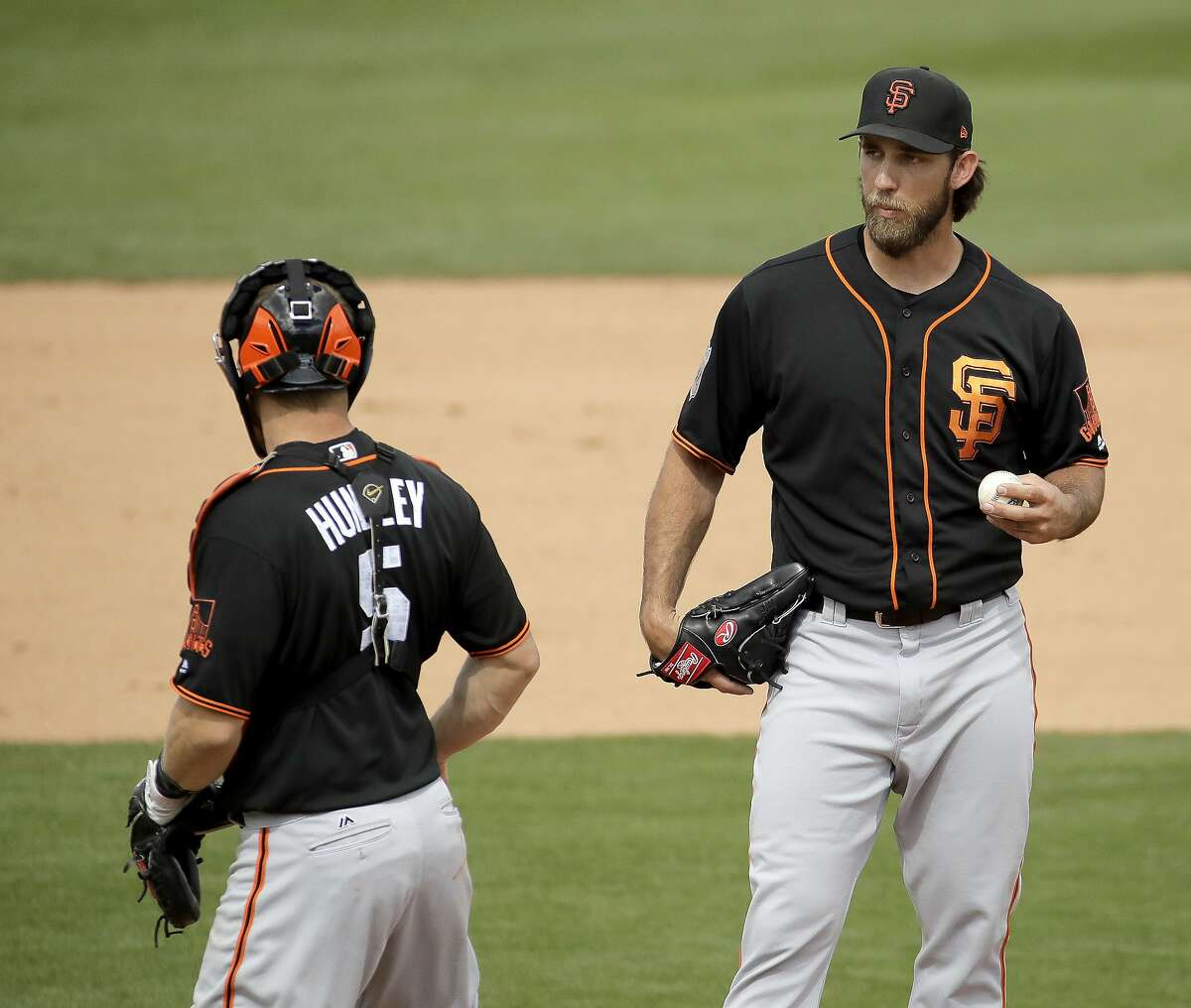San Francisco Giants starting pitcher Madison Bumgarner and catcher Nick Hundley (5) meet on the mound during the second inning of a spring training baseball game against the San Diego Padres Tuesday, Feb. 28, 2017, in Peoria, Ariz. (AP Photo/Charlie Riedel)