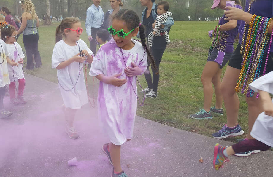 A Good Shepherd Episcopal School student gets blasted with a colorful cloud of purple powder during the Good Shepherd Episcopal School Mardi Gras Color Run in Kingwood Tuesday, Feb. 28. Photo: Melanie Feuk