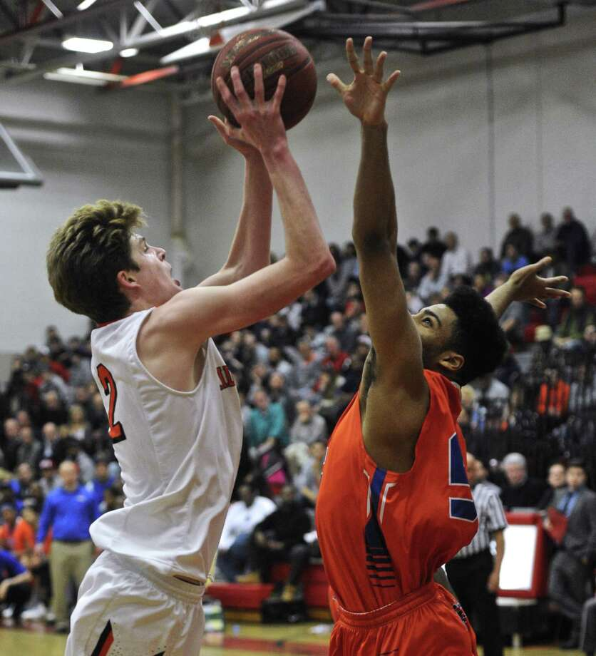 Ridgefield's Brenden McNamara (2) shoots over Danbury's MArcus Fox (55) in the FCIAC boys basketball semifinal game between Danbury and Ridgefield high schools on Tuesday night, February 28, 2017, at Fairfield-Ward High School in Fairfield, Conn. Photo: H John Voorhees III / Hearst Connecticut Media / The News-Times