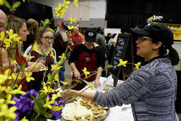 Paula Rodriguez hands out pimento cheese and bacon jam sandwiches at Amelia Farm and Market's booth at the Taste of the Triangle at the Beaumont Civic Center on Tuesday night.  Photo taken Tuesday 2/28/17 Ryan Pelham/The Enterprise