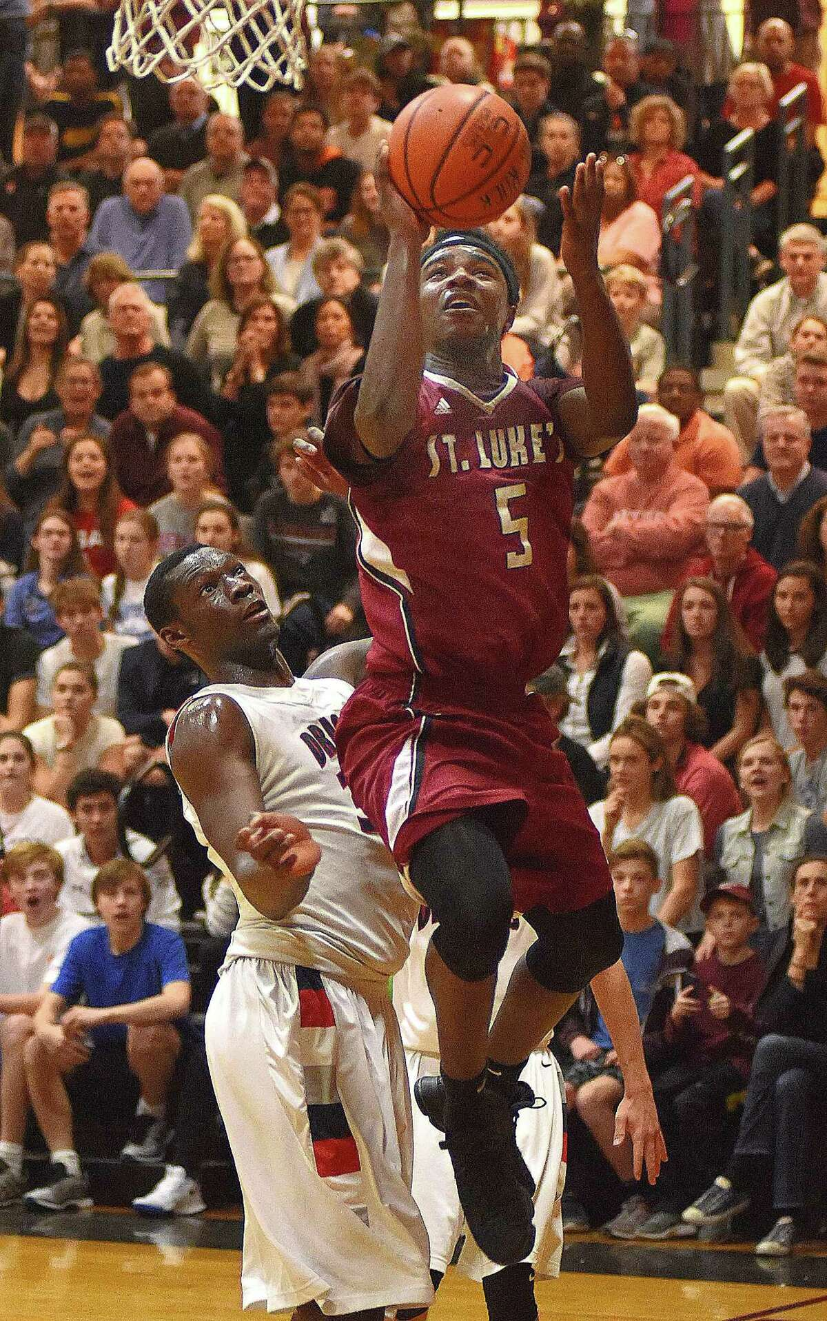 St. Luke's Jonas Harper, right, puts up a runner as he challenges Greens Farms Academy's Sunday Okeke during the first half of Saturday's FAA boys basketball championship at Carey Gym in New Canaan. St. Luke's won the game, 71-69.