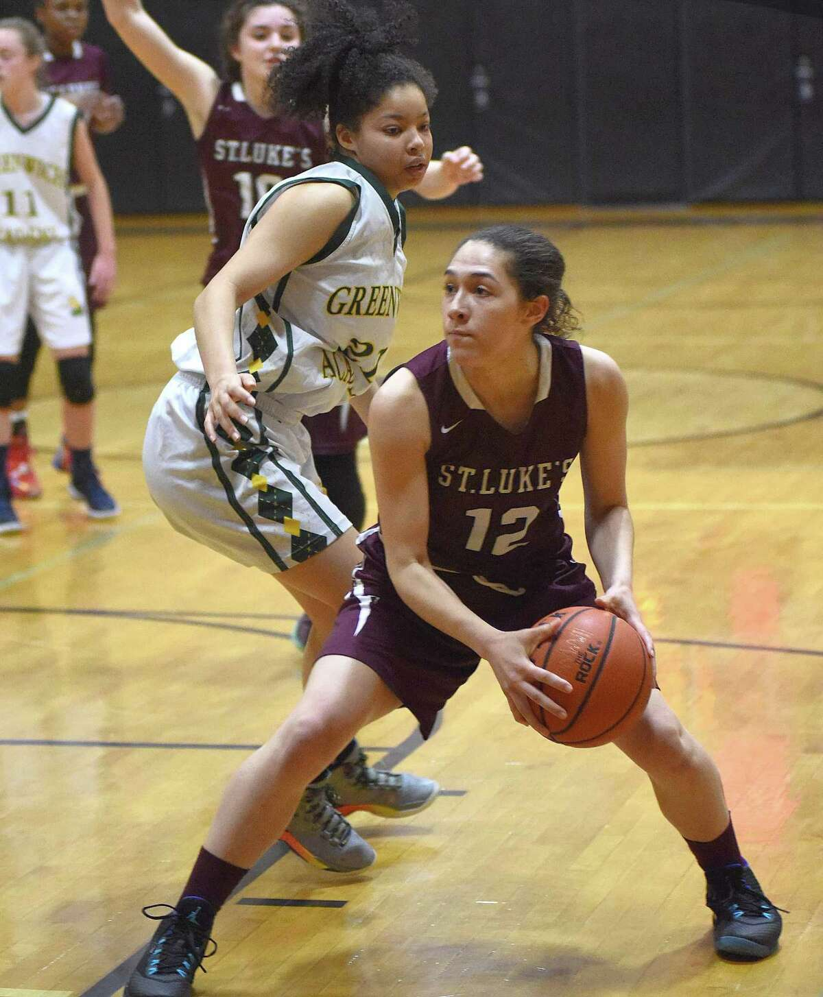 St. Luke's Jada Boggs, right, stops short as Greenwich Academy defender Olivia Davis turns during the first half of Saturday's FAA girls basketball championship game at Carey Gymnasium in New Canaan. St. Luke's won the title with an 82-55 win.