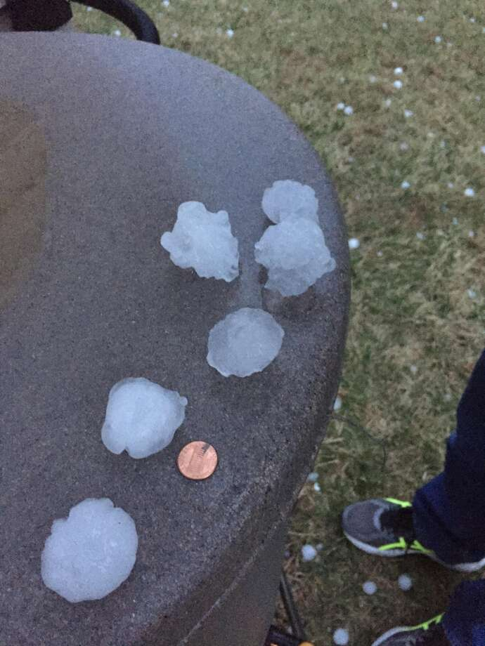 Various hail stones are compared to a penny in Julia Biggs' backyard in Edwardsville. Photo by Julia Biggs.