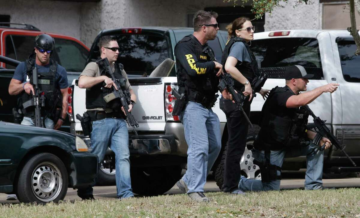 Police search the southwest Houston neighborhood where two officers were shot Tuesday.