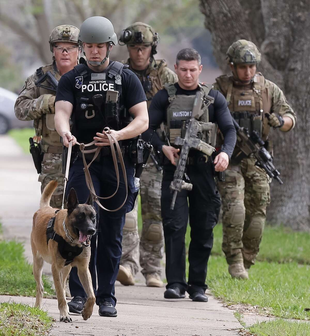 Houston police search the scene in a southwest neighborhood where two officers were shot Tuesday. It was the fourth attack on local police in less than two years.