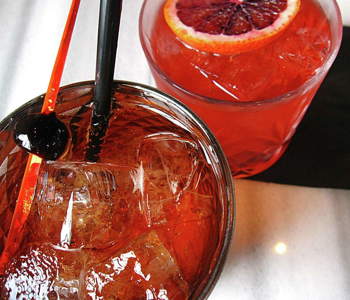 A Battalion Spritz cocktail with prosecco, housemade soda and Aperol (foreground) and a cocktail called the Arsonist, with tequila, Campari, amaretto and blood orange soda from Battalion.