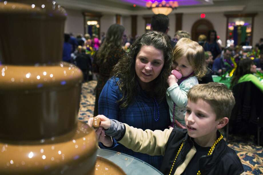 THEOPHIL SYSLO | For the Daily News Alicia Heading, and her children Clayton Heading, 8, and Gabrielle Heading, 2, enjoy snacks from a chocolate fountain provided by Heather 'n' Holly while participating in the Legacy Center's World's Greatest Mardi Gras Feast at The Great Hall Banquet on Tuesday. Photo: Theophil Syslo