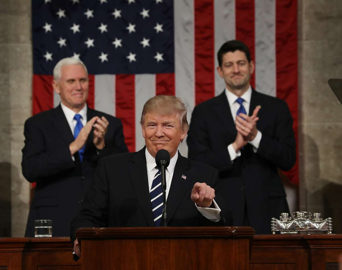 Vice President Mike Pence (left) and Speaker of the House Paul Ryan (right) applaud as U.S. President Donald J. Trump (center) arrives to deliver his first address to a joint session of the U.S. Congress on February 28, 2017 in the House chamber of the U.S. Capitol in Washington, DC. Trump's first address to Congress is expected to focus on national security, tax and regulatory reform, the economy, and healthcare.
