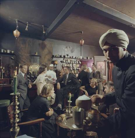 A man in a turban serves a platter of drinks to diners at the Indian House restaurant. Photo: Nat Farbman/The LIFE Picture Collection