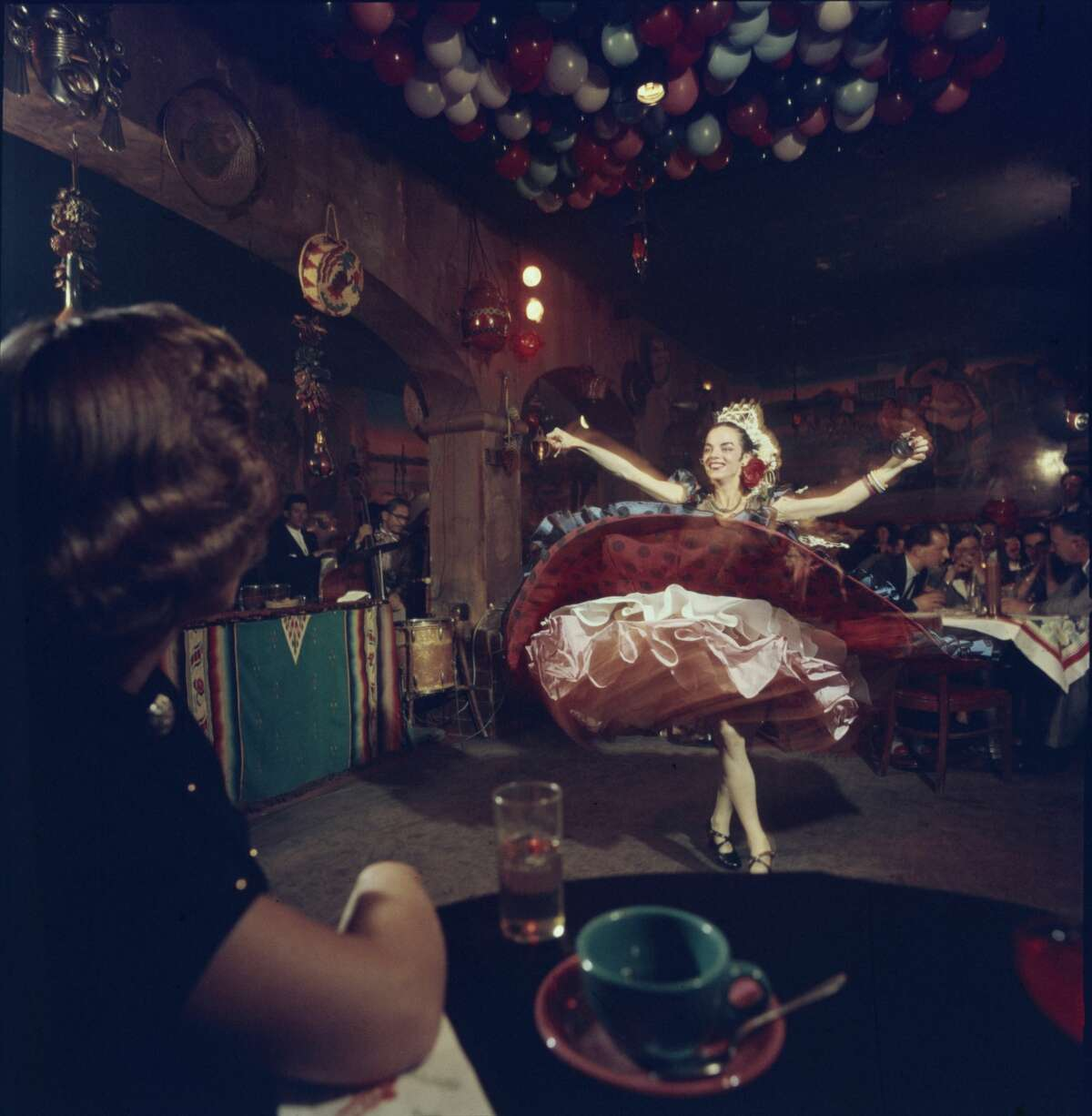 A dancer plays castanets as she twirls her polka-dot skirt and performs a version of a Spanish folk dance for patrons at the Sinaloa Club, San Francisco, California, 1956. (Photo by Nat Farbman/The LIFE Picture Collection/Getty Images)
